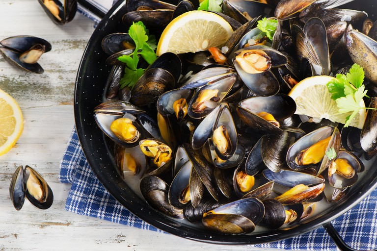 Gourmet mussels served on a napkin garnished with lemon slices.