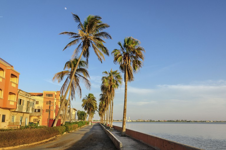 Coastal street with high palm trees during sunset in Saint-Louis, Senegal.