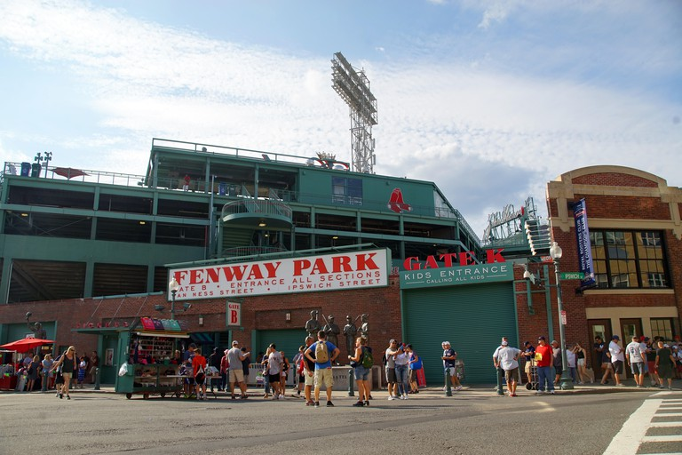 Crowds of fans gather outside to watch a Boston Red Sox baseball game at  Fenway Park, Boston, MA, USA.