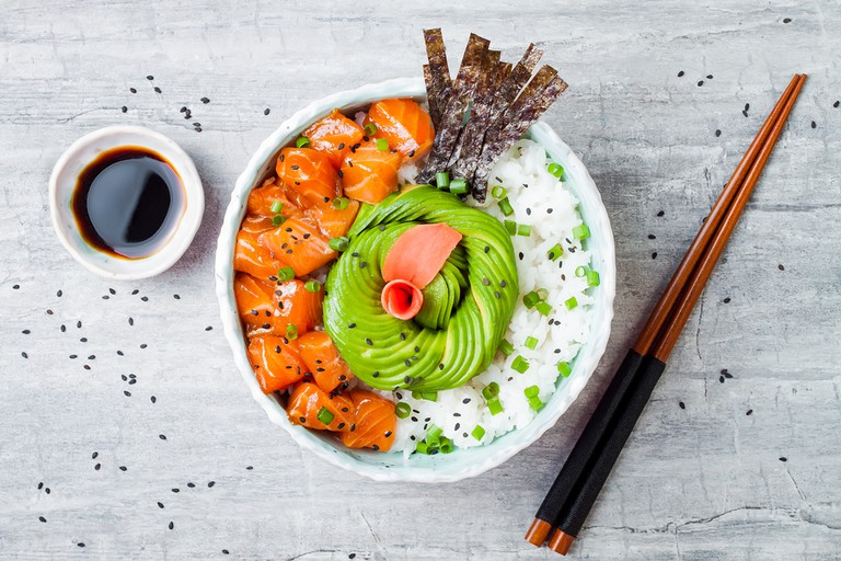 Hawaiian salmon poke bowl with seaweed, avocado rose, and sesame seeds.