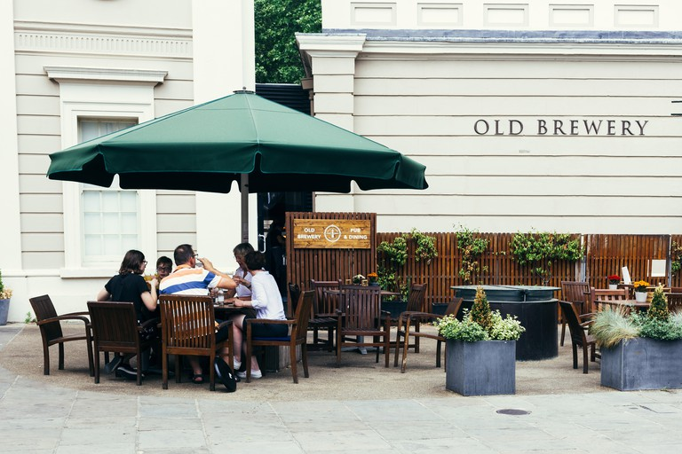 London, UK - July 23, 2018: visitors having lunch in the summer terrace in the Okd Brewery in Greenwich, London, UK