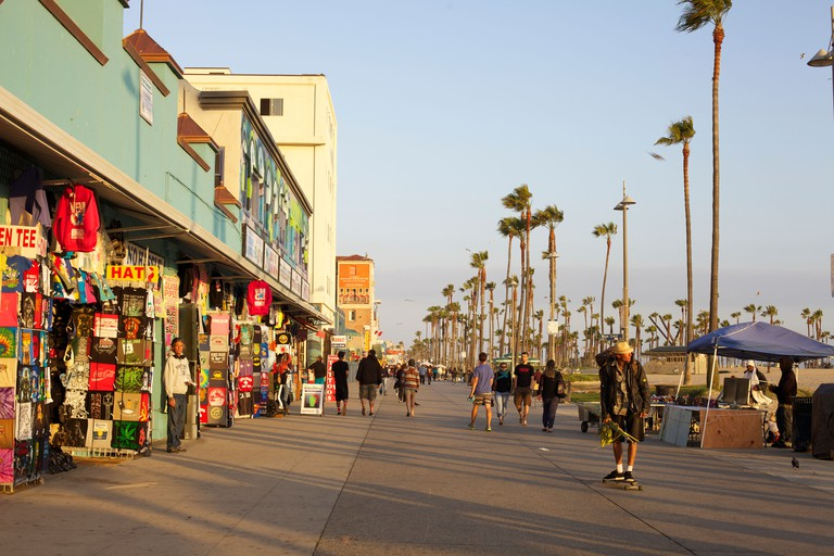 Shoppers walk and a young man skateboards down the sunny Venice Beach Boardwalk in Los Angeles, California.