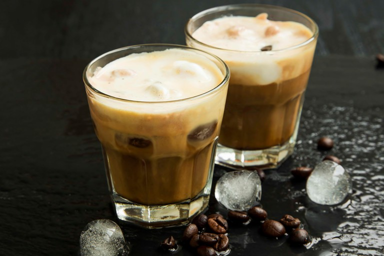 Iced coffee in glasses with ice cubes and coffee beans