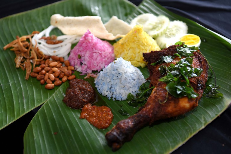 "Colorful plate of banana leaf ""nasi lemak"" or coconut milk spicy rice with fried chicken drumstick, peanuts and anchovies, prawn crackers, cucumber and egg."