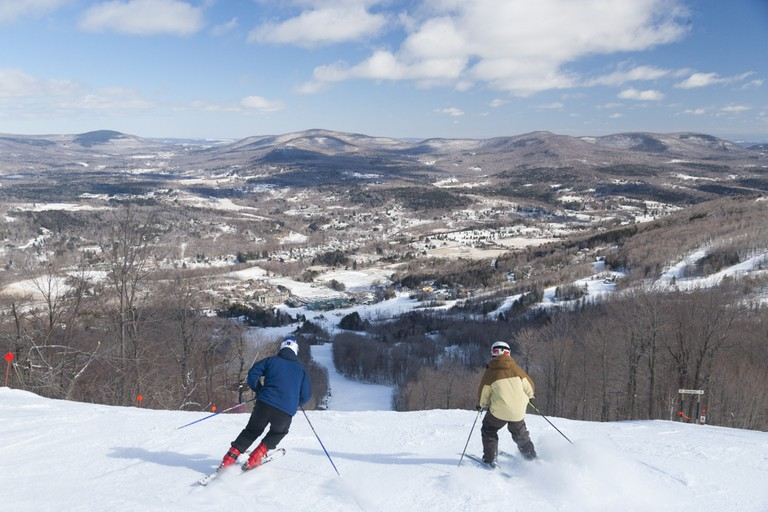 Overlooking the valley with skiers going downhill, Windham, New York, USA.