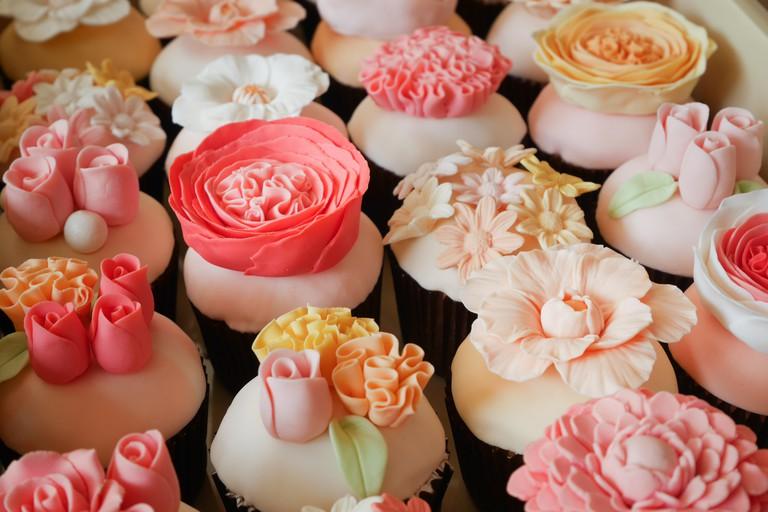 Set of various flower fondant cupcakes.