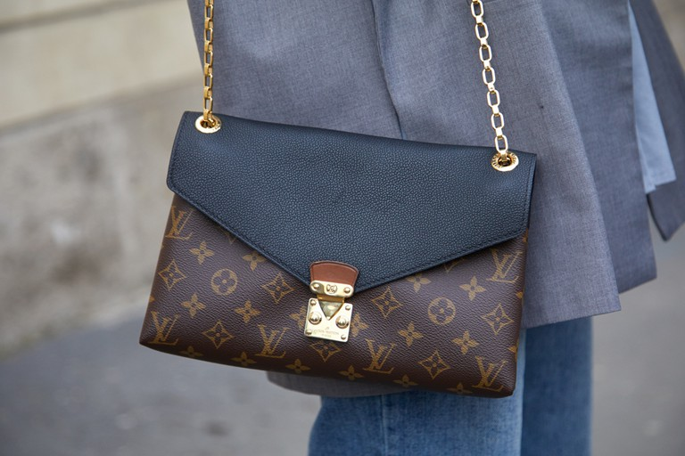 A woman with Louis Vuitton bag as photographed during 2017 Milan Fashion Week.