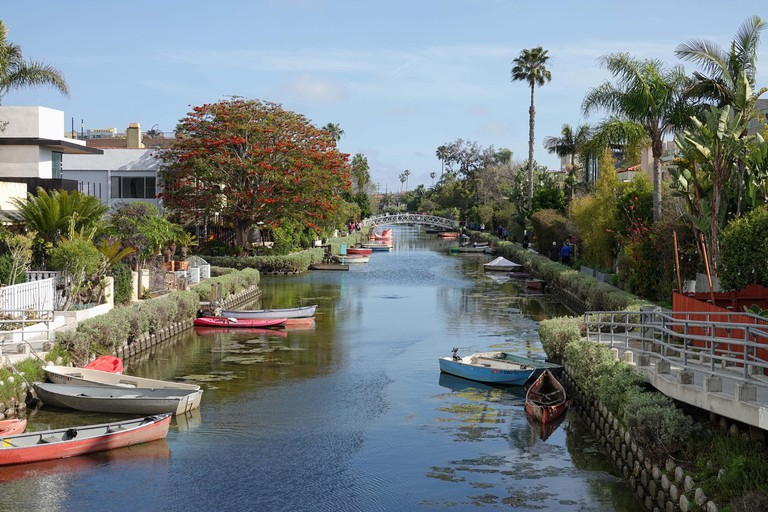 Venice, CA / USA - March 23, 2019: Small boats, homes, and a bridge crossing the water in the Venice Canal Historic District are shown during the day.