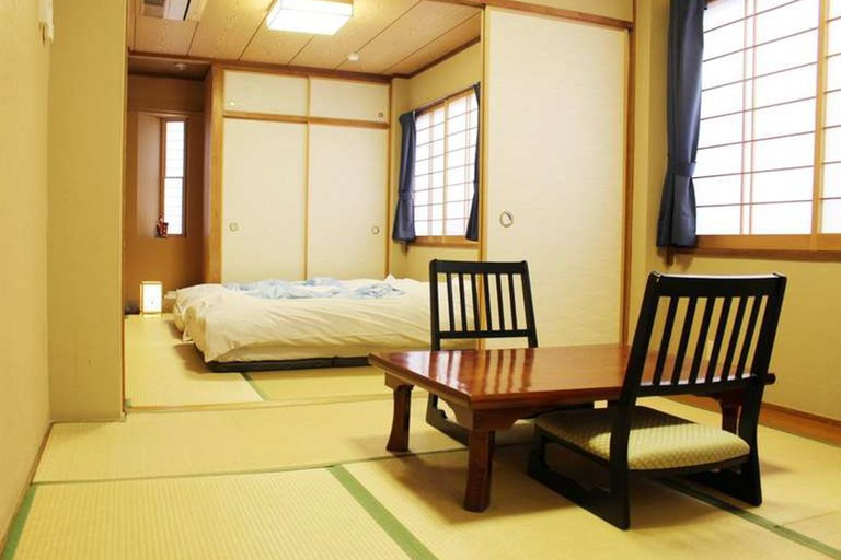 The rooms at Ryokan Kamogawa Asakusa feature tatami flooring and futon bedding