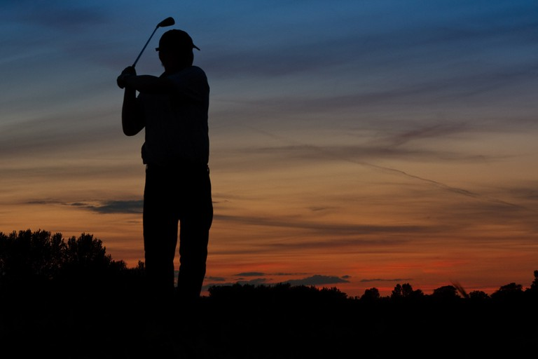 Silhouette of a Golfer teeing off early at dawn