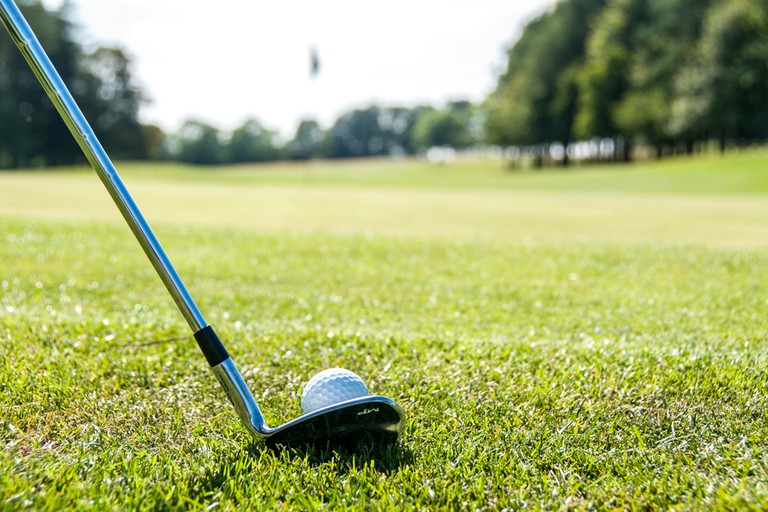 Close up of a golfer chipping a ball toward the flag on the green.