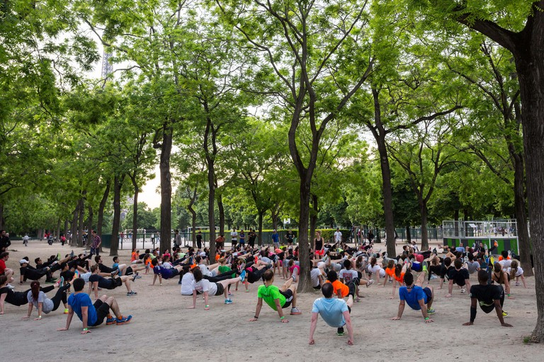 A outdoor class being held in the Champ de Mars park near the Eiffel Tower in Paris.