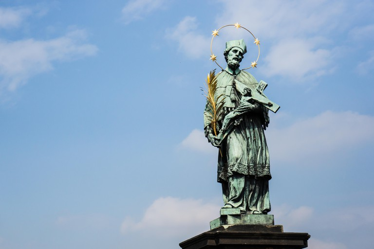 The Statue of St John of Nepomuk stands on the balustrade of the Charles Bridge