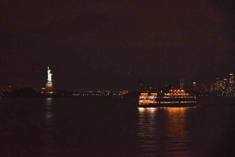 Statue of Liberty and Staten Island Ferry at night, New York City, USA.