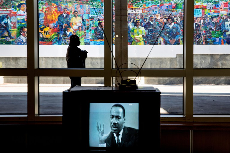An image of Martin Luther King, Jr. is displayed on a vintage television set at the King Center as a visitor stands in front of a mural in the background, in Atlanta, Georgia, USA during the Martin Luther King Holiday.