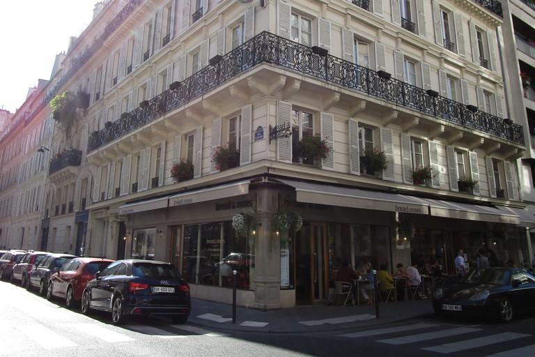 People sit outside of Bread & Roses in Paris