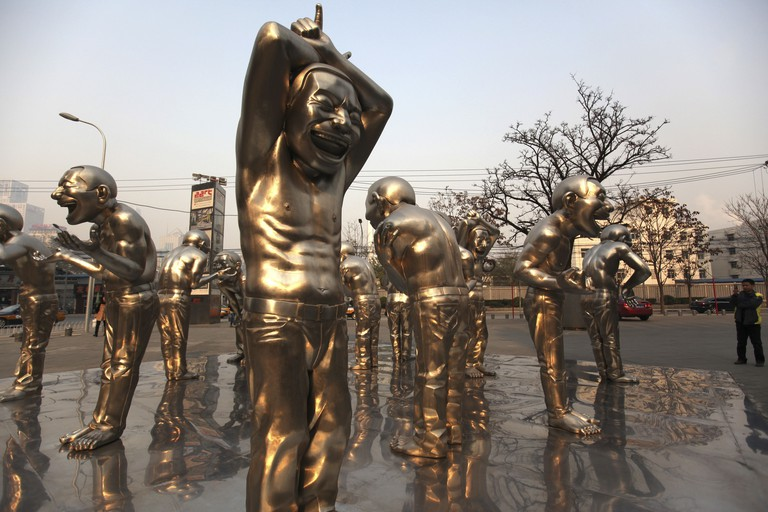 Sculptures by Chinese artist Yue Minjun stand outside the Today Art Museum