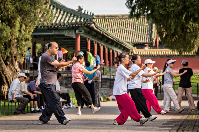 Chinese people practice tai chi martial arts exercise early morning at the Temple of Heaven Park during summer in Beijing