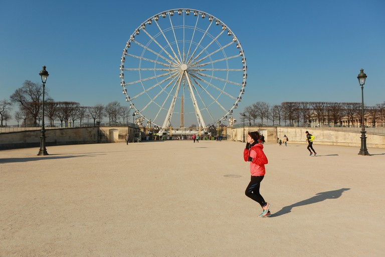 Paris, France - January 20, 2017 : Young Parisian woman makes jogging like many parisian people  in Tuileres Garden located between Louvre Museum and