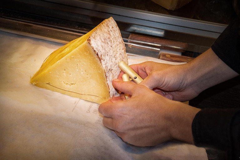 Cheesemonger using traditional wire with handles to cut piece of Emmental cheese