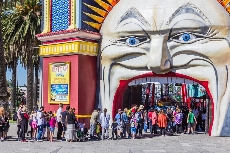 Families wait in a queue to purchase tickets to Luna Park, Melbourne, Australia.