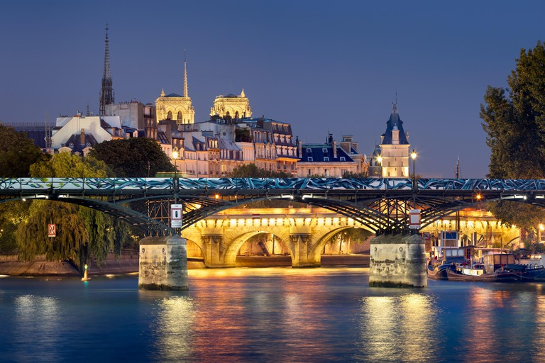 Pont des Arts, Pont Neuf, Notre Dame de Paris Cathedral towers and Seine River at night.