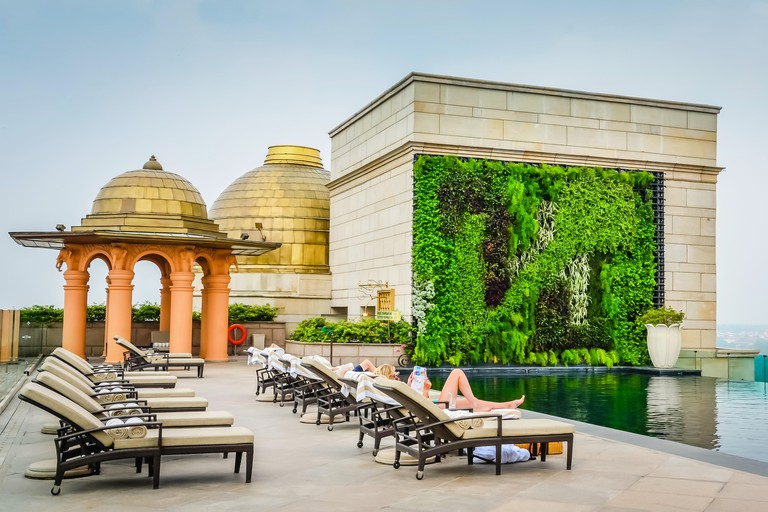 Girl reading a magazine, lounging by the pool, on a luxurious rooftop terrace at the Leela Palace in New Delhi, India.