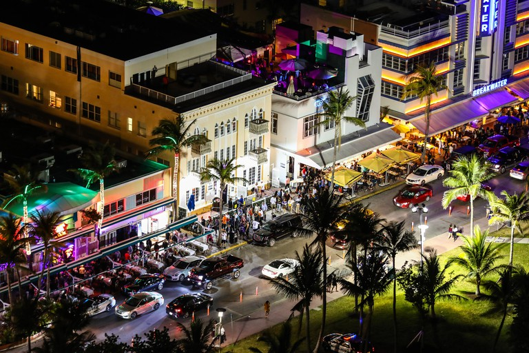 helicopter view over ocean drive, miami, on a busy night with colorful lights showing