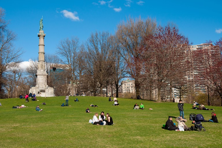The Soldiers and Sailors Monument and people picnicking on the lawn in Boston Common park.