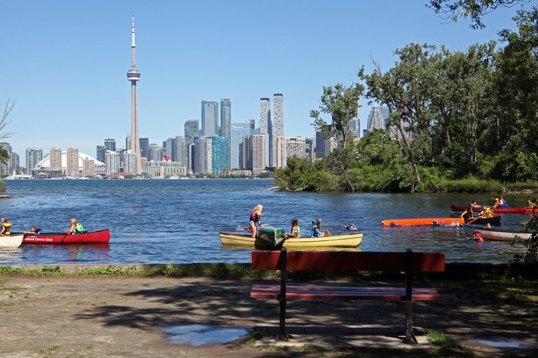 children in canoes on Toronto Islands with the Toronto city skyline in the background, Canada