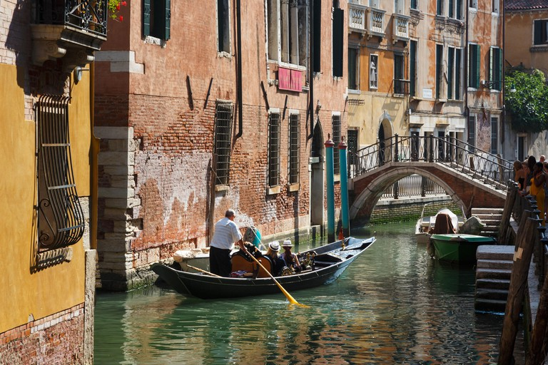 Tourists enjoying gondola ride on canal in Venice
