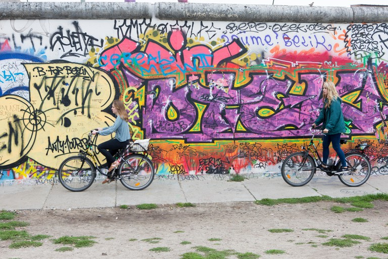 Cycling along side East Side Gallery, Berlin Wall.