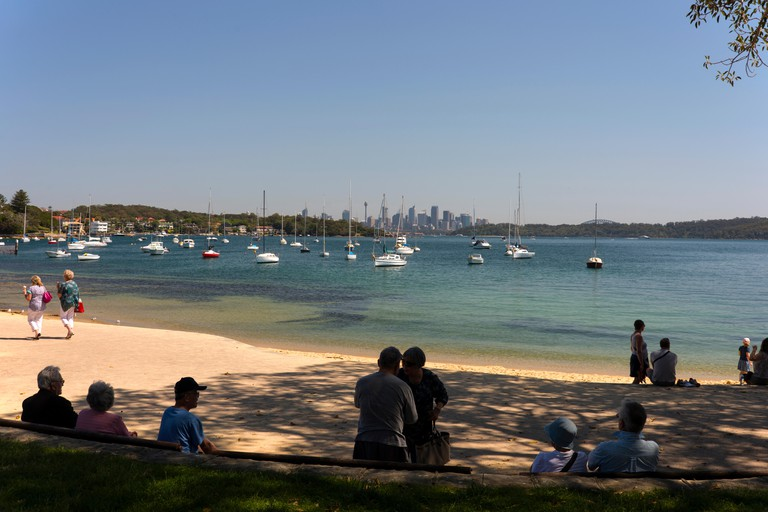 Visitors resting on a small sandy beach in Watson Bay, in New South Wales, Australia
