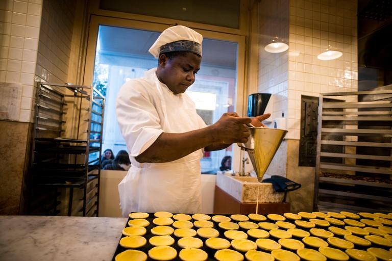 A chef prepares pastel de nata pastries in Lisbon