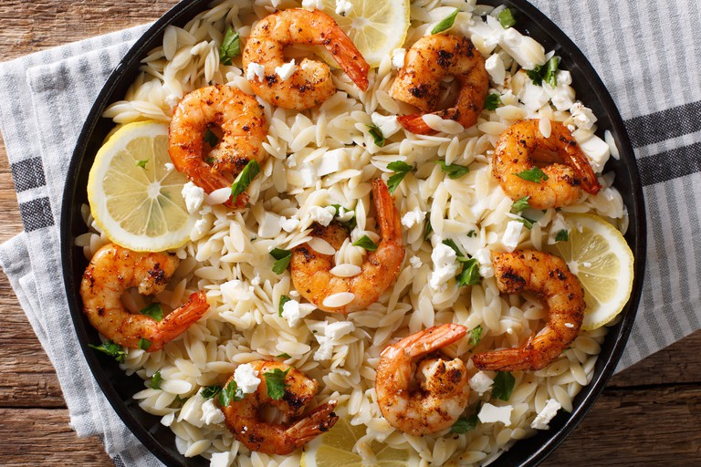 Italian pasta orzo with grilled shrimps, feta cheese and lemon closeup on a plate on the table. horizontal top view from above