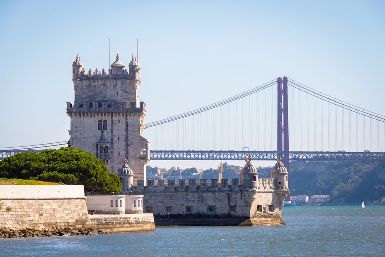 Scenic Belem Tower and wooden bridge miroring with low tides on Tagus River. Torre de Belem is Unesco Heritage and icon of Lisbon and the most visited