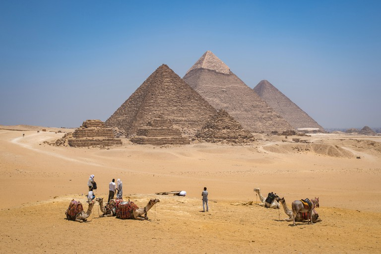 Cairo, Egypt Tourists and camel drivers with their camels resting in the desert with the three Great pyramids of Giza in the bac