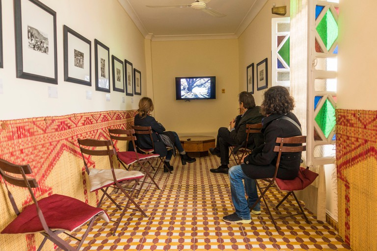 Vistors watching documentary in of House of photography Maison de la Photographie, Marrakech, Morocco.