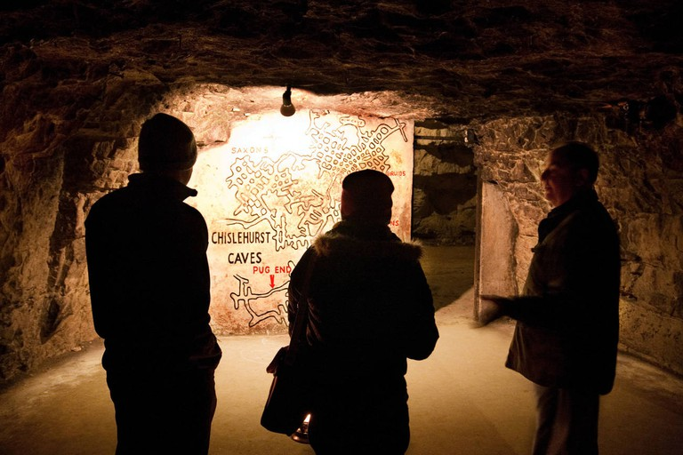 Two people on a tour of the caves are shown a map by their guide; Chislehurst Caves, Chislehurst, Kent, UK