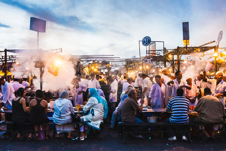 Djemaa el Fna square. People dining at the food stalls at dusk. Marrakesh, Morocco