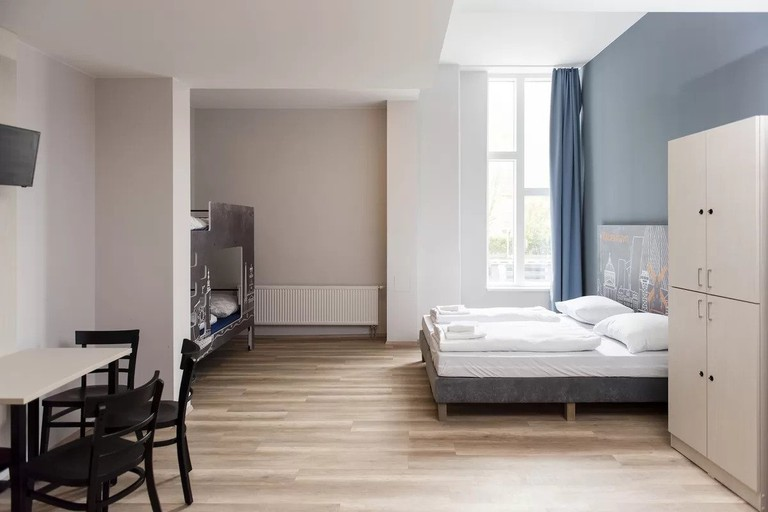 The hotel features rooms with wooden pieces of furniture and traditional Danish art