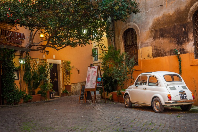 A fiat parked outside a pizzeria in Trastevere