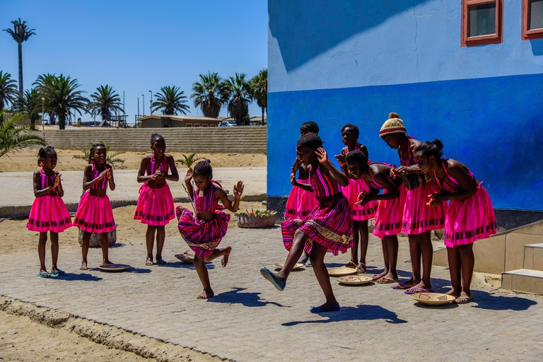 SWAKOPMUND/NAMIBIA - MARCH 25 2018: Pretty young girls in beautiful pink costumes perform song and dance routine outside local school