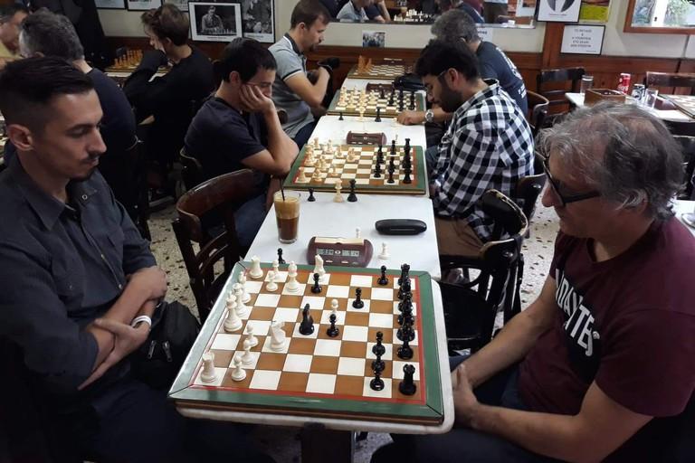 Men play chess at Kafeneio Panellinion in Athens
