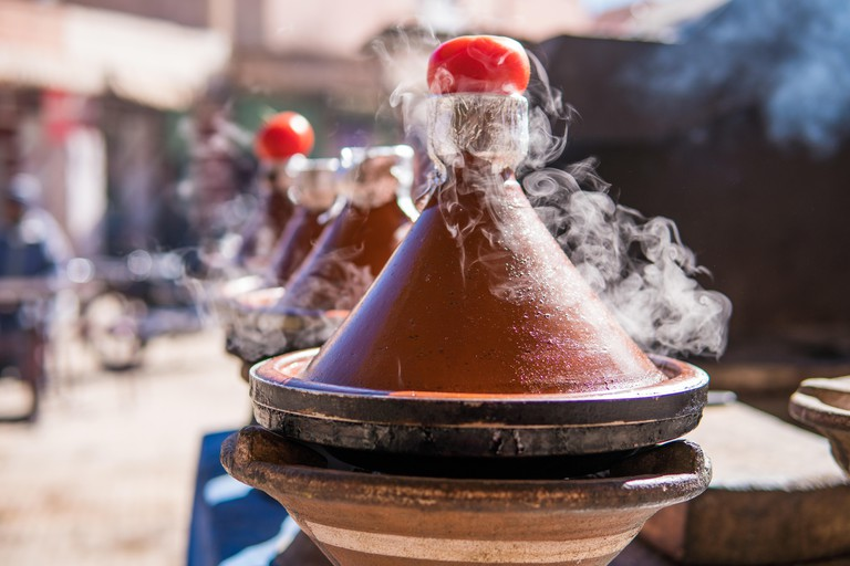 Authentic food of Morocco - traditional Tajine in steam vapor on an outdoor barbecue at town square on the street in Morroco.