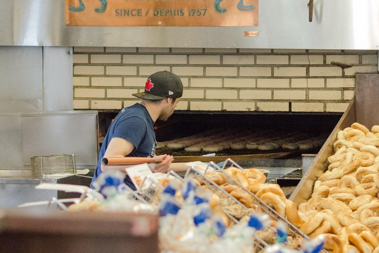 A worker removes fresh Bagels from the oven at St. Viateur Bagel in Montreal Canada.