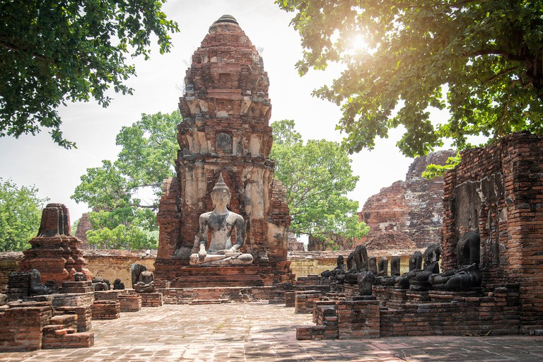 Sitting Buddha at ancient buddhist temple ruins in Ayutthaya, Thailand.