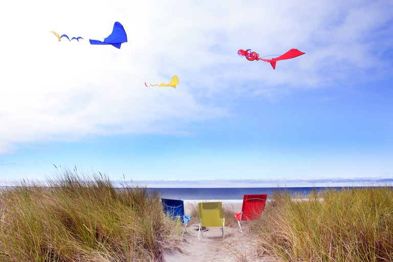 Three colored chairs and kites at the beach