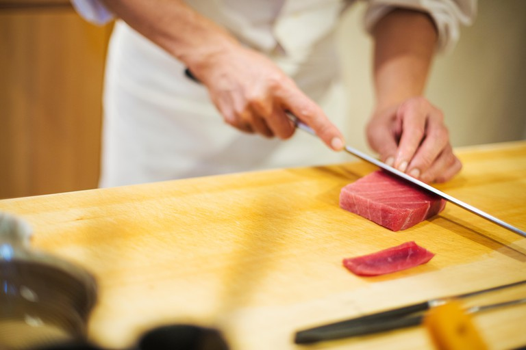 Itamae or master chef, slicing fish with a large knife for making sushi