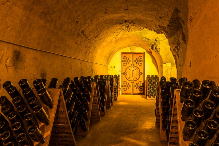 Reims, France - June 12, 2017: the caves of Champagne House Taittinger with old bottles Champagne in pupitres and door of old monastery, France.